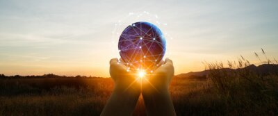Fototapeta 5g and futuristic technology concept.Silhouette a woman use hand holding world,social media networking,cryptocurrency,IoT and blockchain on sunset backgrounds.Elements of this image furnished by NASA