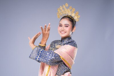 Fototapeta A beautiful Malaysian traditional female dancer with a charming smile performing a cultural dance steps in a traditional outfit. Half length isolated in grey.