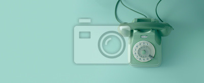 Fototapeta A green vintage dial telephone with green background.