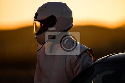 Fototapeta A Helmeted Driver Przygotowuje Się Do Wyścigu Na Wschód Słońca