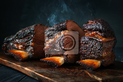 Fototapeta A large steaming fragrant piece of baked beef brisket on the ribs with a dark crust. Classic Texas barbecue