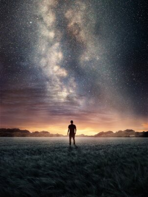 Fototapeta A man Exploring the night sky as the Milky Way galaxy fills the landscape from above. Photo composite