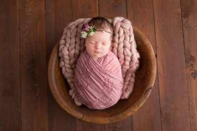 Fototapeta a newborn girl in a wooden basket with a flower wreath. first photo session of a newborn