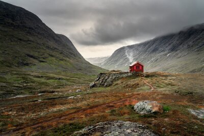 Fototapeta A single small red cabin billows smoke from it's tiny chimney in the remote gorge of central Norway. The distant dark clouds give the feeling of isolation and remoteness. Shot during autumn