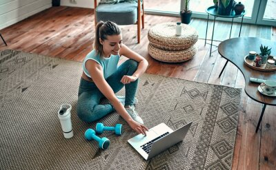 Fototapeta A sporty woman in sportswear is sitting on the floor with dumbbells and a protein shake or a bottle of water and is using a laptop at home in the living room. Sport and recreation concept.