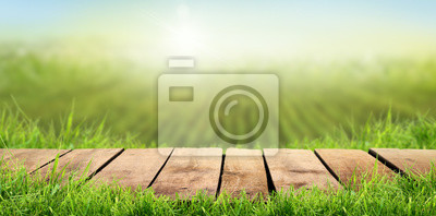 Fototapeta A wooden table with a sunny summers farmland background