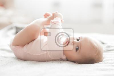 Fototapeta Adorable little baby portrait. Cute baby girl indoor. 6 month child smiling.