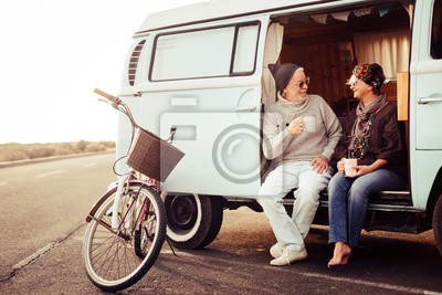 Fototapeta Adult aged caucasian happy couple sit down out of a vintage van drinking a tea and enjoying the outdoor leisure activity during travel vacation - bike parked near the vehicle