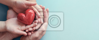 Fototapeta adult and child hands holding red heart on aqua background, heart health, donation, CSR concept, world heart day, world health day, family day, fair trade