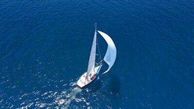 Fototapeta Aerial drone top down photo of beautiful sailing boat cruising in deep blue Atlantic open ocean sea
