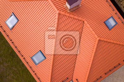Fototapeta Aerial top view of house metal shingle roof, brick chimneys and small plastic attic windows. Roofing, repair and renovation work.