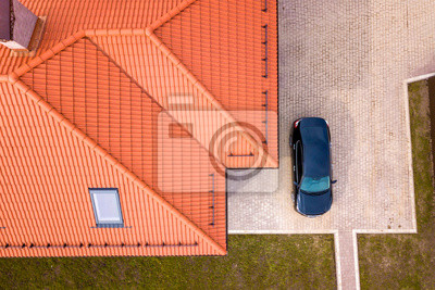Fototapeta Aerial top view of house metal shingle roof with attic windows and black car on paved yard.