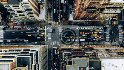 Fototapeta Aerial view of New York downtown building roofs. Bird's eye view from helicopter of cityscape metropolis infrastructure, traffic cars, yellow cabs moving on city streets and crossing district avenues