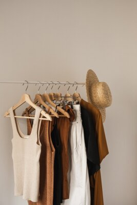 Fototapeta Aesthetic minimalist fashion influencer blog composition. Stylish pastel summer female clothes, dress, tops, t-shirts, straw hat on clothing rack against white wall. Fashion women wear