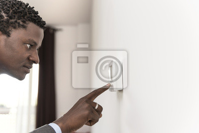 African american man push button digital thermostate