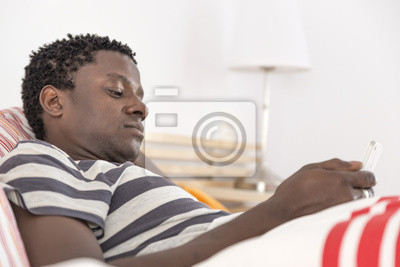 African american man with his phone in bed