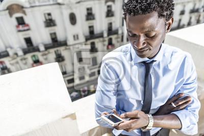 African biznesmen z smartphone na balkon.