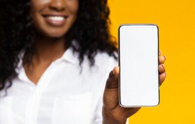 Fototapeta African millennial woman showing blank cellphone screen