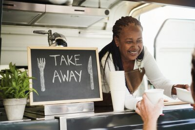 Fototapeta African woman serving takeaway food with eco paper boxes inside food truck - Small business owners concept - Focus on face