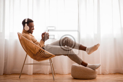 Fototapeta Afro Guy In Headphones Using Smartphone Sitting On Chair Indoor