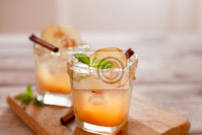 Fototapeta Apple cider cocktail with cinnamon and apple traditional autumn and winter drink