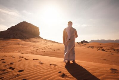 Fototapeta Arab man stands alone in the desert and watching the sunset.
