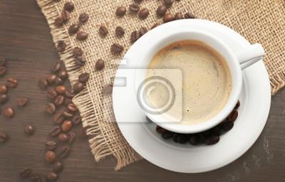 Aromatyczne filiżankę kawy z prażoną fasolką na wory