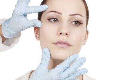 Fototapeta Arzt überprüft das Gesicht der Patientin vor dem Eingriff