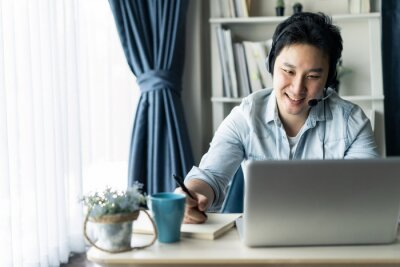 Fototapeta Asian businessman talking to colleague team in video call conference writing note on book with smile face. Man using computer laptop and headphone for online meeting. Smart working from home concept.