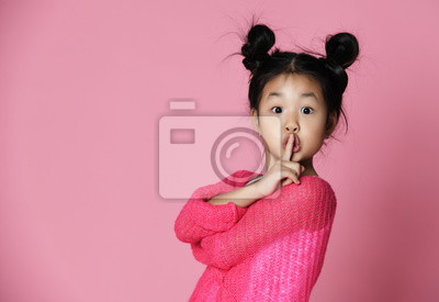 Fototapeta Asian kid girl in pink sweater shows shh sign Close up portrait