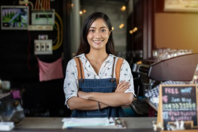 Fototapeta Asian women Barista smiling and using coffee machine in coffee shop counter - Working woman small business owner food and drink cafe concept