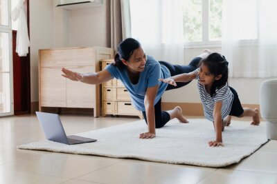 Fototapeta Asian young mother and her daughter doing stretching fitness exercise yoga together at home. Parent teaching child work out to be strong and maintain physical health and wellbeing in daily routine.