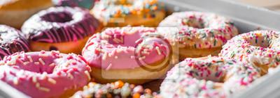 Fototapeta Assorted sweet donuts in a paper box.