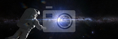 Fototapeta astronaut in outer space flying towards the center of the Milky Way galaxy