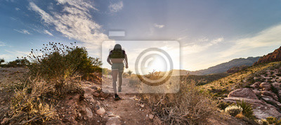 Fototapeta athletic african american woman hiking through red rock canyon in nevada at sunset