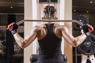 Fototapeta Athletic młoda kobieta pokazując mięśnie pleców.