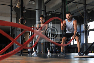 Fototapeta Athletic young couple with battle rope doing exercise in functional training fitness gym.