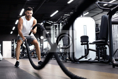 Fototapeta Athletic young man with battle rope doing exercise in functional training fitness gym.