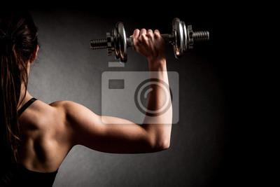 Fototapeta Atrakcyjna kobieta fit pracuje obecnie z hantlami jako Concep siłowni