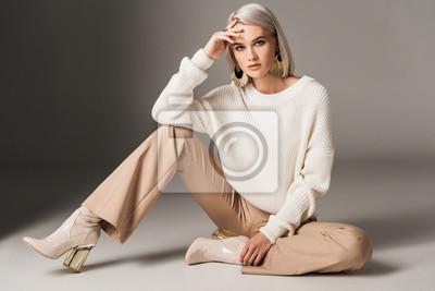 Fototapeta atrakcyjna kobieta modny pozowanie w biały modny sweter, beżowe spodnie i obcasy jesienią, na szaro