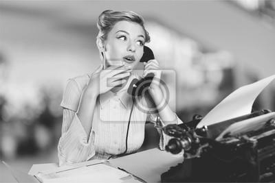 Fototapeta Atrakcyjna młoda kobieta mówi na vintage telefonu