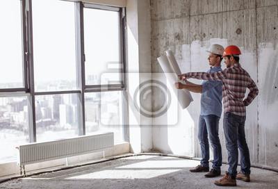 Fototapeta atrakcyjny architekt i inżynier w kasku budowlanym planują swoją pracę. prace architektoniczne. zdjęcie z boku
