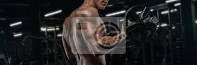 Fototapeta Attractive tall muscular bodybuilder doing heavy deadlifts in moder fitness center.