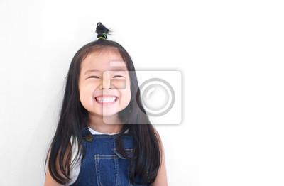 Fototapeta Azjatyckie dzieci słodkie lub dziecko dziewczynka i przedszkola uczeń szczęśliwy uśmiech białe zęby i śmiać się z nosić dżinsowe dżinsy dla mody na białym tle z miejsca na białym tle