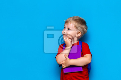 Fototapeta Back to school Portrait of happy surprised kid in glasses isolated on blue background with copy space. new school knowledges
