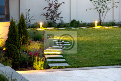 Fototapeta backyard of the mansion with a flowerbed and a lawn of green grass with a marble walkway of square tiles in the evening with a garden lighting with decorative ground lamps illuminating a warm light.