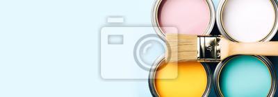 Fototapeta Baner koncepcji remontu. Pędzel z drewnianym uchwytem na otwartych puszkach na niebieskim pastelowym tle. Kolory żółty, biały, różowy, turkusowy. Makro