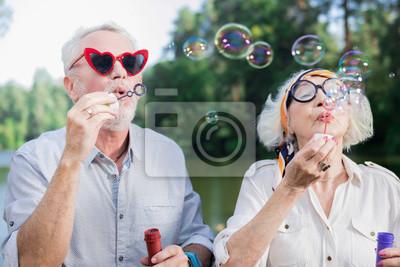 Fototapeta Bańki mydlane. Śmieszna aktywna para emeryci stoi na moscie i dmucha mydlanych bąble