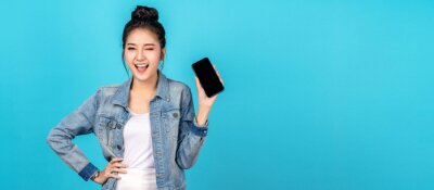 Fototapeta Banner of asian woman feeling happiness, blinks eyes and standing hold smartphone on blue background. Cute asia girl smiling wearing casual jeans shirt and connect internet shopping online and present