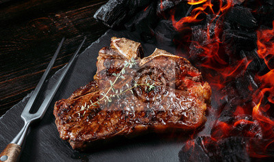 Fototapeta barbeque steak on a black slate board with meat fork and grill coals next to it